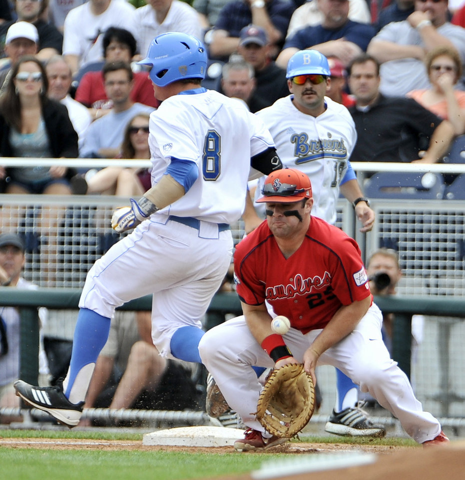 Photo -   UCLA's Tyler Heineman (8) is safe at first base as Stony Brook first baseman Kevin Courtney (25) bobbles the ball in the first inning of an NCAA College World Series baseball game in Omaha, Neb., Friday, June 15, 2012. (AP Photo/Eric Francis)