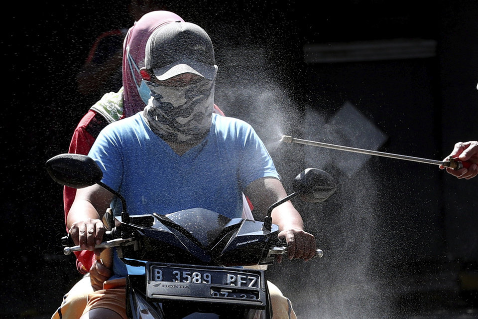 Photo -  Motorists are sprayed with disinfectant in an attempt to curb the spread of coronavirus outbreak at the gate of a housing complex in South Tangerang, Indonesia, Tuesday, March 31, 2020. Indonesia will close its doors to foreign arrivals in an attempt to curb the coronavirus spread while the country plans to bring home more than a million nationals working abroad. (AP Photo/Tatan Syuflana)