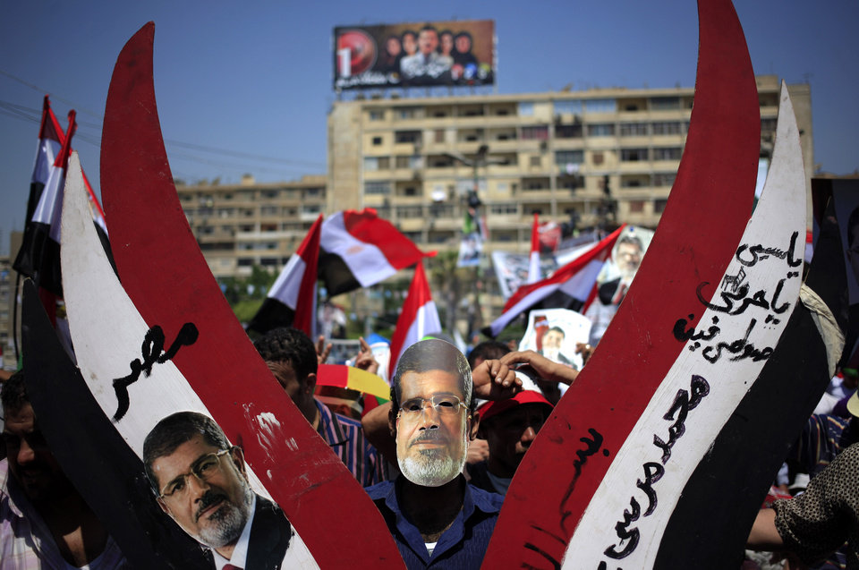 Photo - Supporters of Egypt's ousted President Mohammed Morsi hold pictures of him and chant slogans during a protest at Nasr City, where protesters have installed their camp and hold their daily rally, in Cairo, Egypt, Friday, July 26, 2013. Political allies of Egypt's military lined up behind its call for huge rallies Friday to show support for the country's top general, Abdel-Fattah el-Sissi, pushing toward a collision with Islamist opponents demanding the return of Mohammed Morsi, the nation's ousted president. Arabic writing reads,