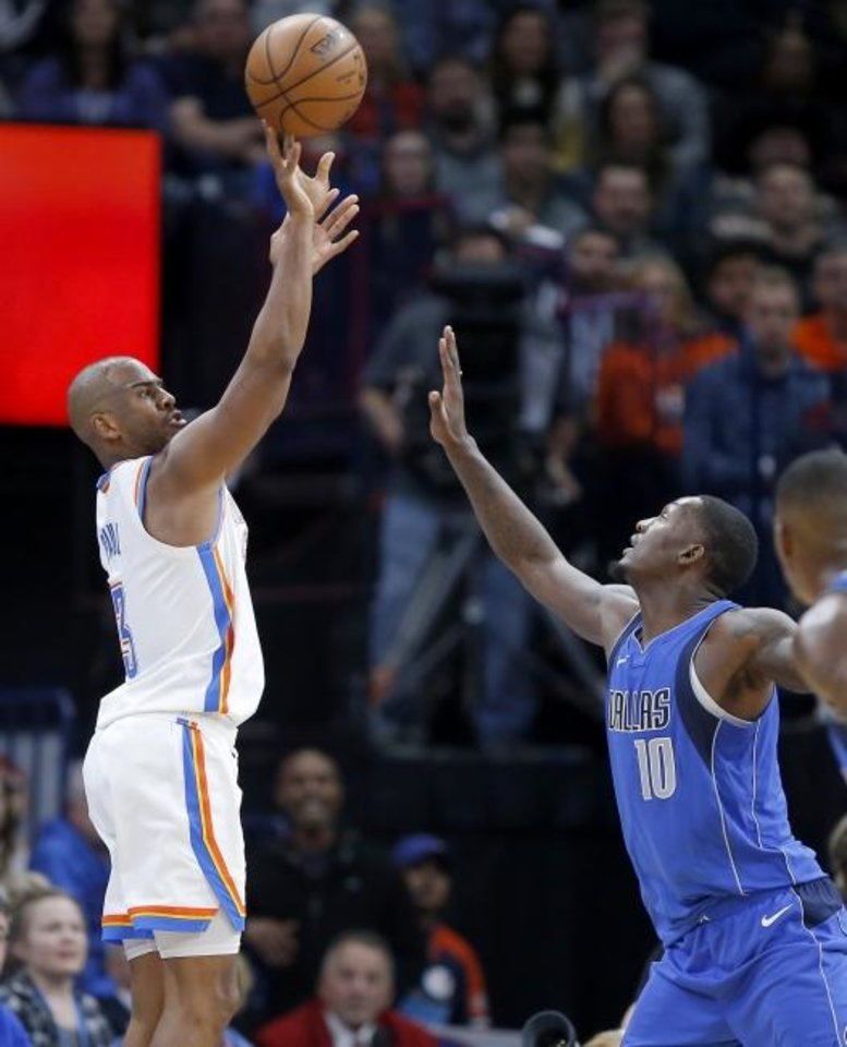 Photo -  Oklahoma City's Chris Paul, left, shoots a basket over Dallas' Dorian Finney-Smith during Tuesday night's game at Chesapeake Energy Arena. Paul scored 13 points in the fourth quarter to lead OKC to a 106-101 win. [Bryan Terry/The Oklahoman]