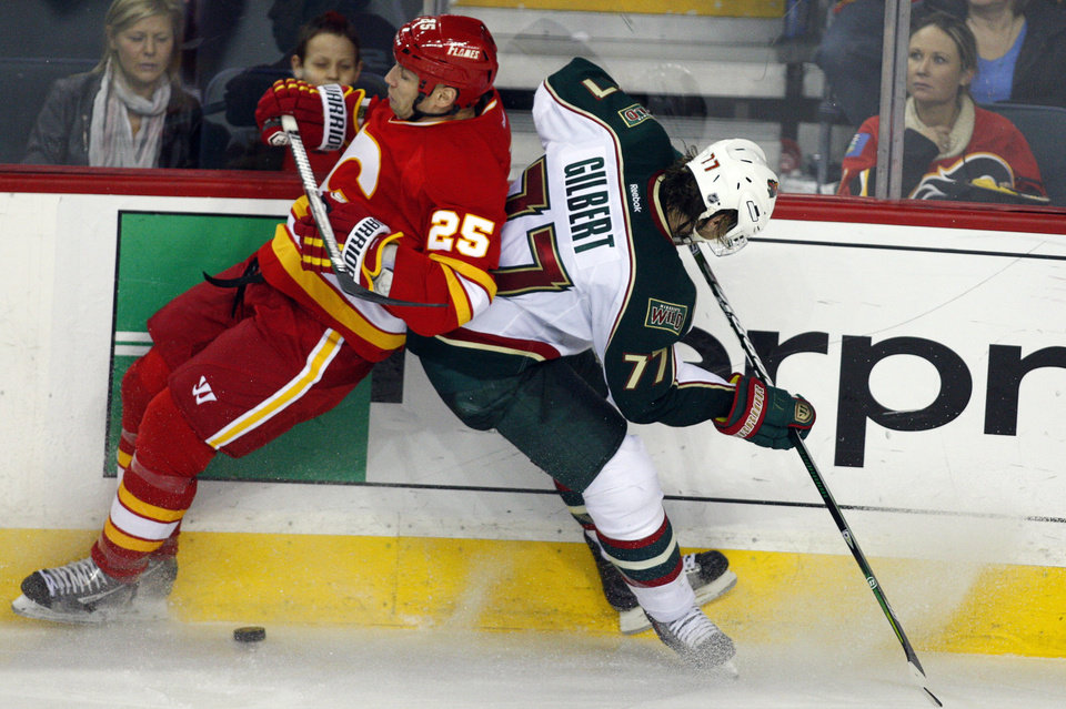 Photo - Minnesota Wild's Tom Gilbert, right, collides with Calgary Flames' Steve Begin during the third period of an NHL hockey game in Calgary, Alberta, Saturday, Feb. 23, 2013. (AP Photo/The Canadian Press, Jeff McIntosh)
