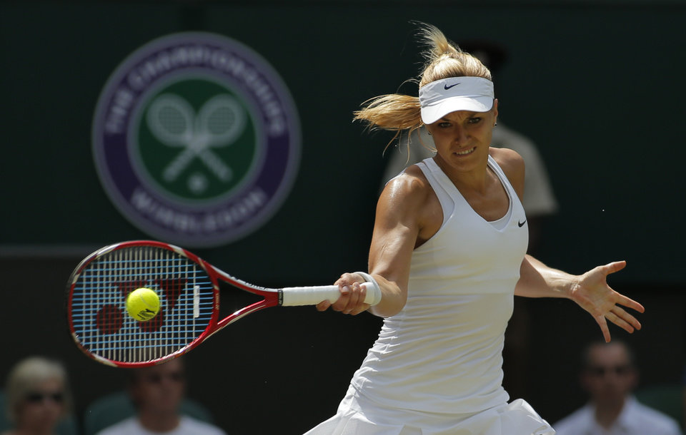 Photo - Sabine Lisicki of Germany plays a return to Simona Halep of Romania during their women's singles quarterfinal match at the All England Lawn Tennis Championships in Wimbledon, London, Wednesday, July 2, 2014. (AP Photo/Pavel Golovkin)
