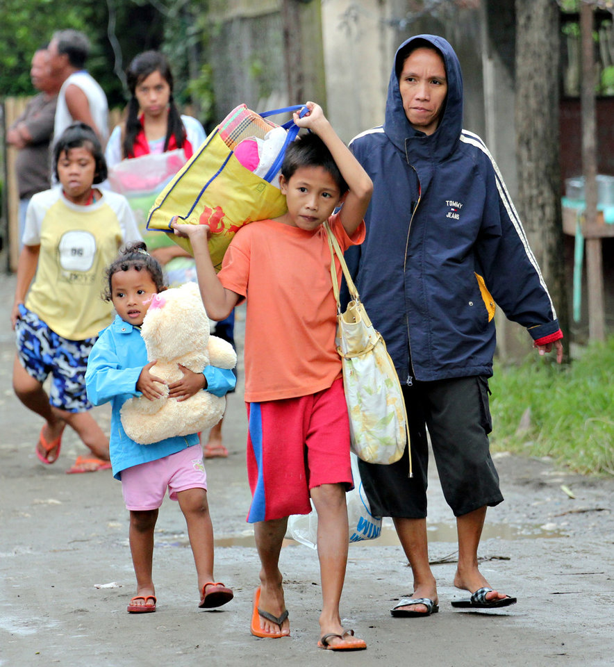 Residents evacuate to safer grounds in anticipation of Typhoon Bopha in Butuan city in southeastern Philippines Tuesday, Dec. 4, 2012. Typhoon Bopha, one of the strongest typhoons to hit the Philippines this year, barreled across the country's south on Tuesday, killing dozens of people and forcing more than 50,000 to flee from inundated villages. (AP Photo/Erwin Mascarinas)