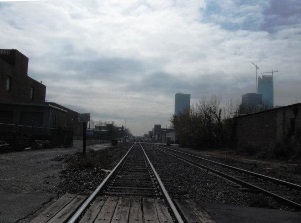 Photo - The downtown skyline can be seen in the distance as the Burlington Northern Santa Fe railrway runs paralell to Automobile Alley.  Steve Lackmeyer