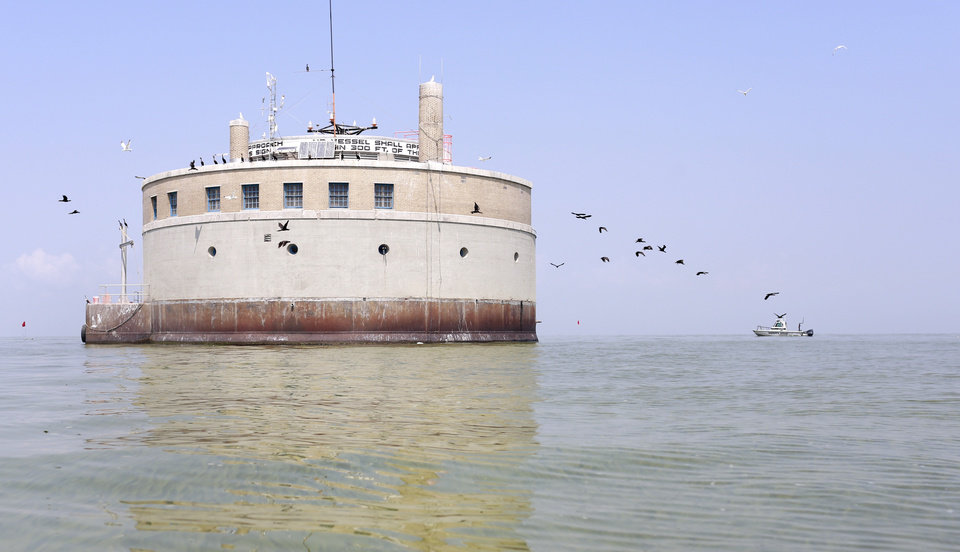 Photo - Birds fly near the City of Toledo water intake crib, Sunday, Aug. 3, 2014, in Lake Erie, about 2.5 miles off the shore of Curtice, Ohio. More tests are needed to ensure that toxins are out of Toledo's water supply, the mayor said Sunday, instructing the 400,000 people in the region to avoid drinking tap water for a second day. Toledo officials issued the warning early Saturday after tests at one treatment plant showed two sample readings for microcystin above the standard for consumption, possibly because of algae on Lake Erie. (AP Photo/Haraz N. Ghanbari)