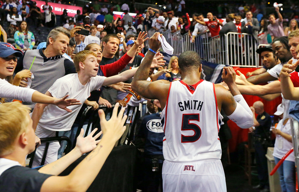 Photo - Atlanta Hawks fan give game hero Josh Smith high fives as he leaves the court after leading the Hawks to a 102-91 victory over the Pacers in Game 4 of their first-round NBA basketball playoff series game Monday, April 29, 2013, in Atlanta. The win ties the first round series 2-2.   (AP Photo/ Journal-Constitution, Curtis Compton)