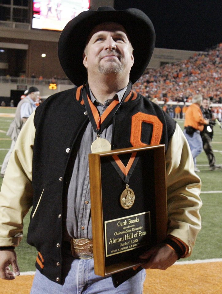 Photo - Garth Brooks walks away with his plaque after a ceremony during the second half of the college football game between Oklahoma State University (OSU) and the University of Missouri (MU) at Boone Pickens Stadium in Stillwater, Okla. Saturday, Oct. 17, 2009.  Photo by Steve Sisney, The Oklahoman