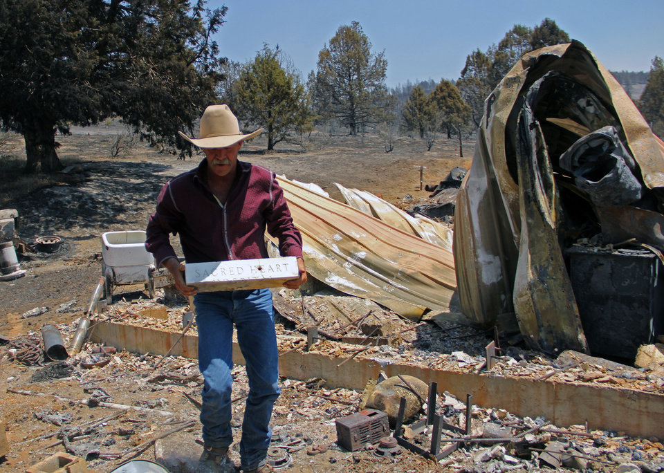 Photo - Sprague River, Ore., resident David Pool lifts a marble block from the rubble left by the Moccasin Fire, Tuesday, July 15, 2014. The stone, which came from the hospital where his oldest son was born, is one of the few items at his home not destroyed by the blaze. (AP Photo/The Herald and News, Lacey Jarrell)