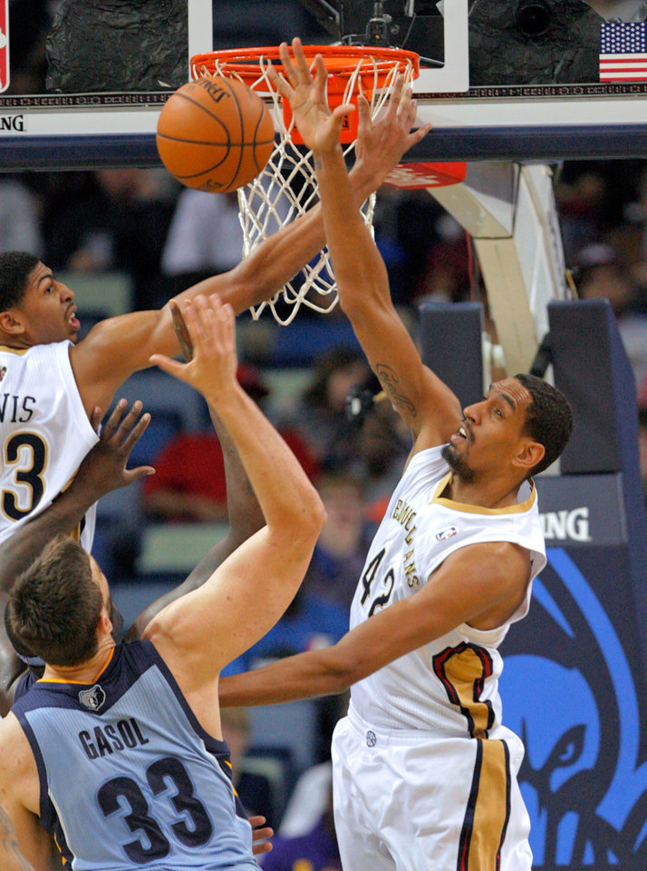Photo - New Orleans Pelicans forward Anthony Davis (23) and center Alexis Ajinca (42) lose a rebound to Memphis Grizzlies center Marc Gasol (33) in the first half of an NBA basketball game in New Orleans, Wednesday, March 12, 2014. (AP Photo/Scott Threlkeld)