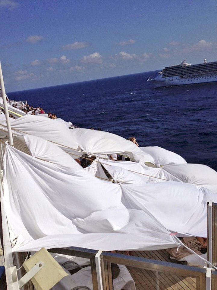 Photo - This Sunday, Feb. 10, 2013 photo, provided by Kalin Hill, of Houston, shows passengers with makeshift tents on the the deck of the Carnival Triumph cruise ship at sea in the Gulf of Mexico. The ship nearing Mobile Bay is without engine power and is being towed by tugboats. (AP Photo/Kalin Hill)
