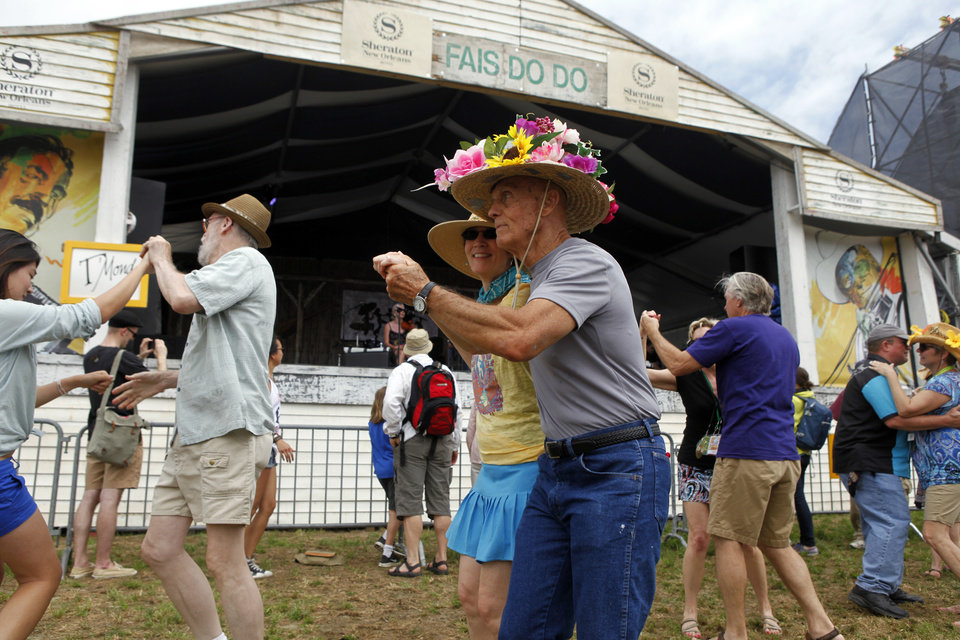 Photo - Robert Gale, wearing a festive flowered hat, dances with Liz Lindahl in front of the Fais Do Do Stage during the New Orleans Jazz and Heritage Festival in New Orleans, Friday, April 26, 2013. The Metairie, La. couple were dancing to the music of  the Cajun band T'Monde during the opening day of the annual festival. (AP Photo/Doug Parker)
