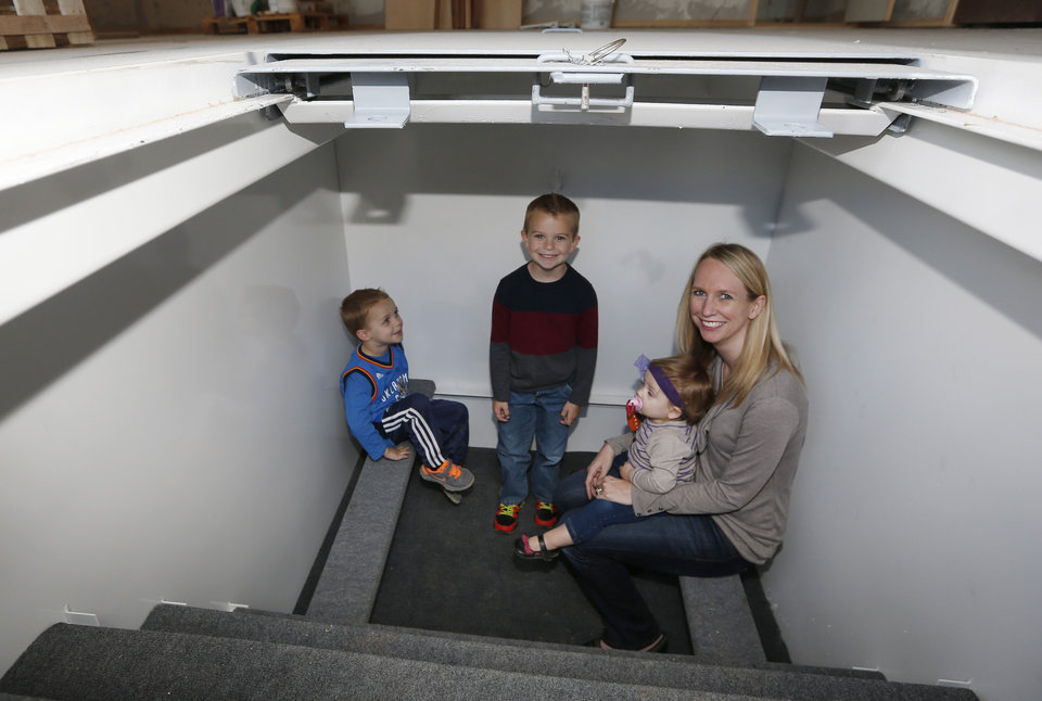 Photo - In this Thursday, May 1, 2014 photo, Tessa Beaulieu poses for a photo in the storm shelter of her new construction home with her children, from left, Hudson, Dawson and Sloane, in Edmond, Okla. Last year's deadly tornadoes, which killed more than 30 people, scared Oklahomans in a way that previous storms had not, moving them to add tornado shelters or reinforced safe rooms to their homes. In fact, surging demand has overwhelmed companies that build the shelters. (AP Photo/Sue Ogrocki)
