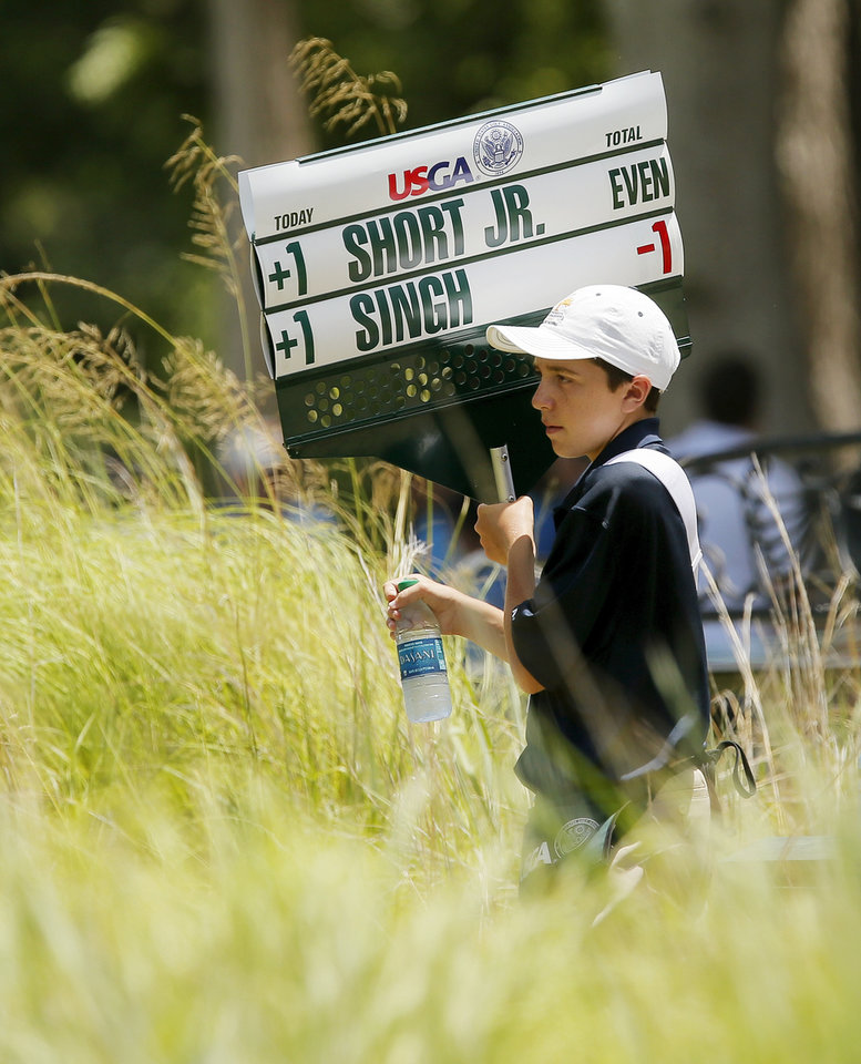 Photo - Riley Funk, 14, of Atchison, Kansas, grabs a bottle of water between No. 5 and No. 6 as he carries the sign for Wes Short Jr. and Vijay Singh during the third round of the U.S. Senior Open golf tournament at Oak Tree National in Edmond, Okla., Saturday, July 12, 2014. Photo by Nate Billings, The Oklahoman