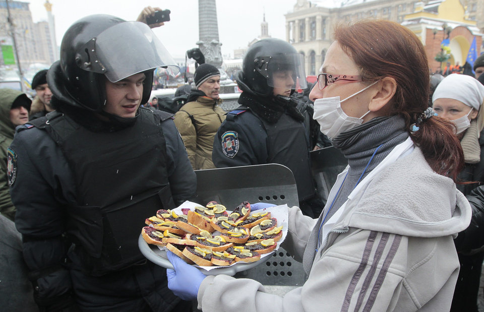 Photo - A Pro-European Union activist tries to give food to riot police officers preparing to block the Independence Square in KIev, Ukraine, Monday, Dec. 9, 2013. The policemen, wearing helmets and holding shields, formed a chain across Kiev's main street outside the city building. Organizers called on protesters to vacate the city hall and the other building which the opposition had used as its headquarters. (AP Photo/Sergei Chuzavkov)