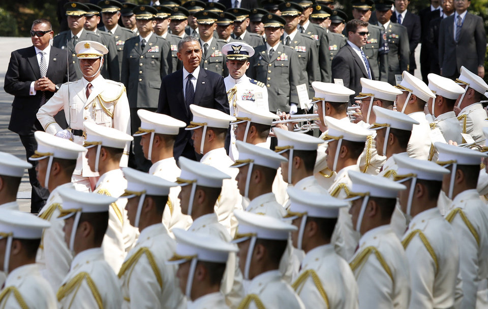 Photo - U.S. President Barack Obama, center, inspects an honor guard during a welcoming ceremony at the Imperial Palace in Tokyo Thursday, April 24, 2014. Facing fresh questions about his commitment to Asia, Obama will seek to convince Japan's leaders Thursday that he can deliver on his security and economic pledges, even as the crisis in Ukraine demands U.S. attention and resources elsewhere. (AP Photo/Yuya Shino, Pool)