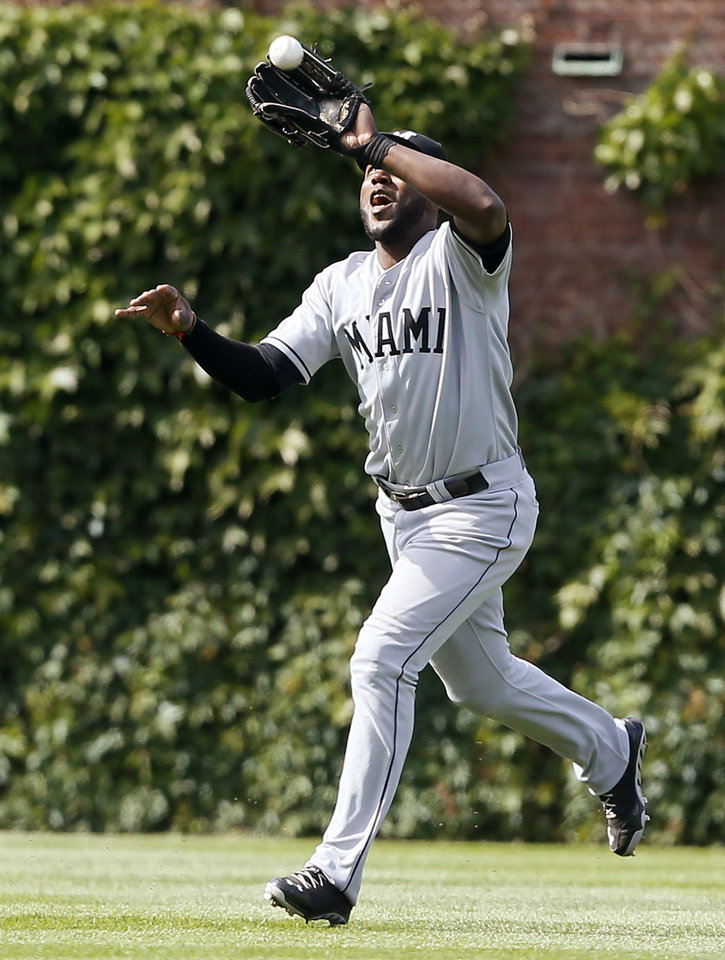 Photo - Miami Marlins center fielder Marcell Ozuna catches a fly ball hit by the Chicago Cubs' Emilio Bonifacio during the eighth inning of a baseball game on Sunday, June 8, 2014, in Chicago. (AP Photo/Andrew A. Nelles)