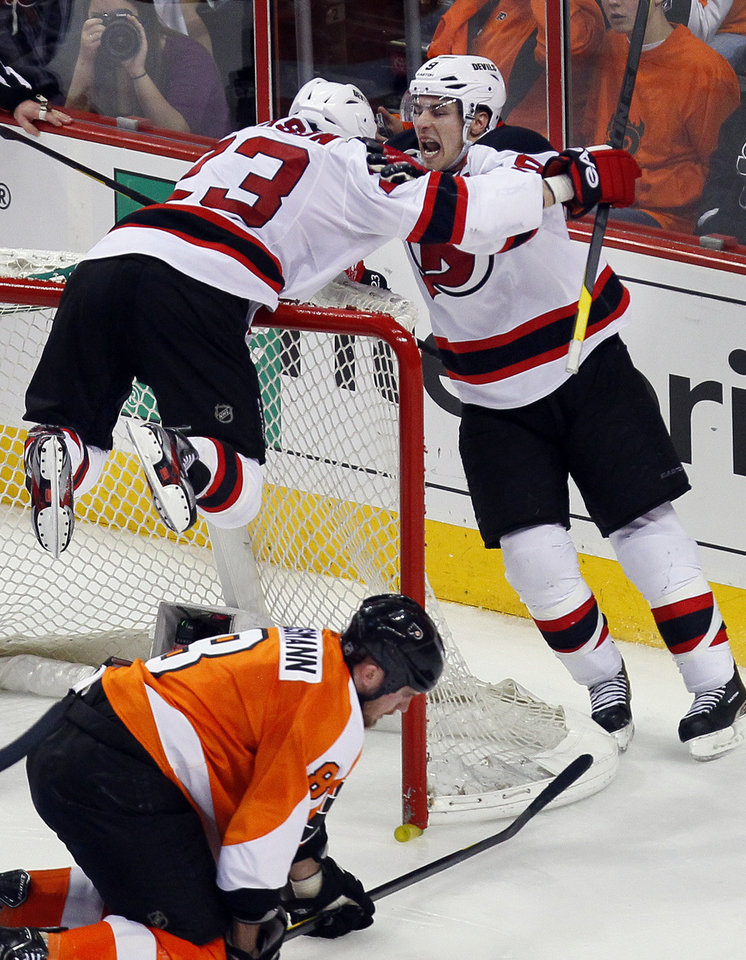 Photo -   New Jersey Devils' Zach Parise, right, and David Clarkson, laying on the net, who scored what would be the game-winning goal celebrate during the third period in Game 2 of an NHL hockey Stanley Cup second-round playoff series with the Philadelphia Flyers, Tuesday, May 1, 2012, in Philadelphia. Flyers, Nick Grossmann kneels down in the crease. The Devils won 4-1 tying the best of seven series at 1-1.(AP Photo/Tom Mihalek)