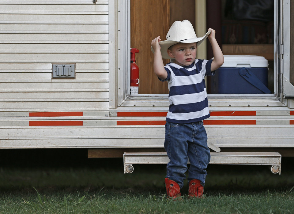 Matt Casteel, 2, of Lucien, adjusts his cowboy hat outside his family's trailer at Edmond's annual LibertyFest Rodeo, which kicks off a 13-day celebration leading up to the Fourth of July. PHOTO BY BRYAN TERRY, THE OKLAHOMAN. <strong>Bryan Terry - THE OKLAHOMAN</strong>