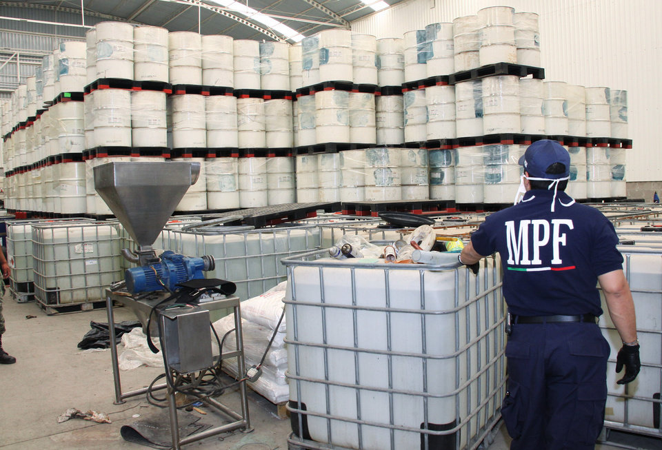 "FILE - In this June 20, 2011, photo released by Mexico's Attorney General's office, police from the Federal Public Ministry looks at drums of precursor chemicals for methamphetamine that were seized in Queretaro, Mexico. Mexican drug cartels are flooding U.S. cities with cheap, extraordinarily pure methamphetamine made in factory-like ""super labs� _ a surge in production that has all but negated the nation's long effort to curb meth production at home with tighter controls on key ingredients.(AP Photo/Attorney General's office, File)"