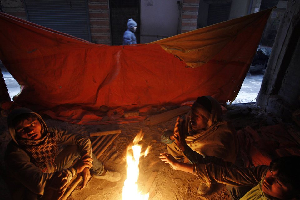 Indian laborers sit near a fire in New Delhi, India, Tuesday, Jan. 8, 2013. North India continues to face below average weather conditions with dense fog affecting flights and trains. More than 100 people have died of exposure as northern India deals with historically cold temperatures. (AP Photo/Tsering Topgyal)