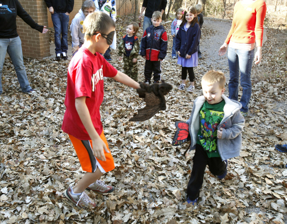 "Photo - Above: Dillon Griggs, 9, left, and Holden Kleckner, 4, play a game of ""Bat and Butterfly,"" as they learn about using senses other than sight at Martin Park Nature Center in Oklahoma City.Photo by  PAUL HELLSTERN,  The Oklahoman"