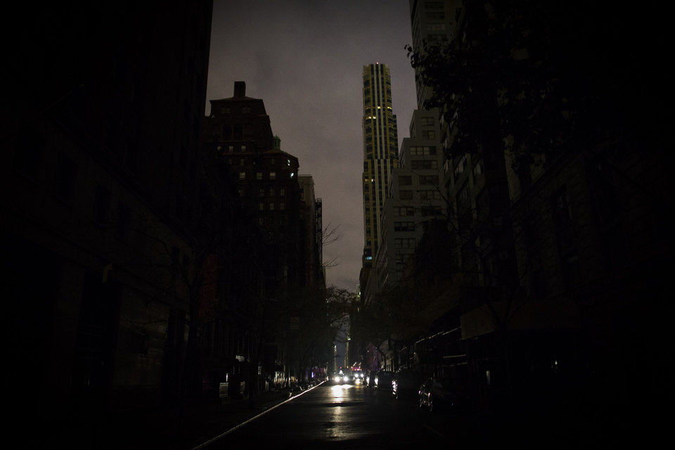 A lone taxi drives through the darkened canyons of New York's lower Manhattan neighborhood after Superstorm Sandy slammed into the eastern seaboard, setting off a cascade of flooding, fires, and power outages throughout the metropolitan area and beyond, Friday, Nov. 2, 2012. (AP Photo/John Minchillo)
