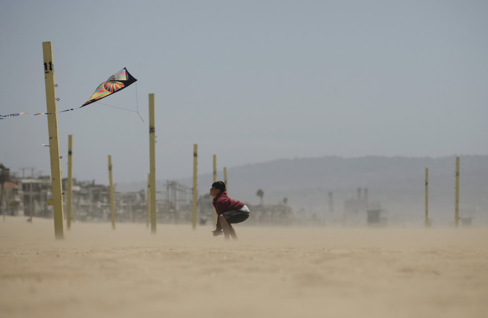 Photo - Christian Ahn, 11, flies a kite in Manhattan Beach, Calif., Monday, April 8, 2013. Strong winds have begun raking parts of Southern California. The National Weather Service says the gusty northwest-to-north winds will become widespread across the region Monday and continue into the night. (AP Photo/Jae C. Hong)