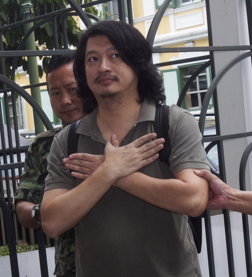 Photo - Sombat  Boonngam-anong gestures a sign of freedom upon arriving at the military court in Bangkok, Thailand, Thursday, June 12, 2014. Sombat was arrested last Thursday after failing to report himself to the authorities as was ordered by the military government that took power in Thailand last month. A prominent social activist, he had spearheaded an online campaign calling for people to silently show opposition to the coup by raising a three-finger salute in public places - borrowing a symbol of resistance to oppression from Hollywood's