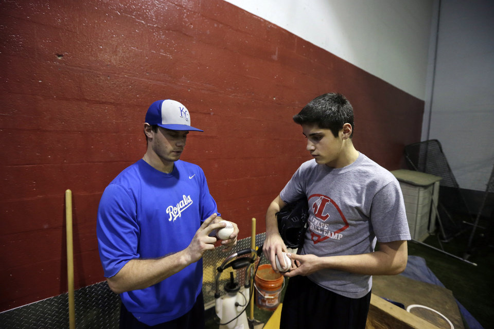 Photo - In this Feb. 24, 2014 photo, Kansas City Royals minor league pitcher,  John Walter, left, of Haddonfield, N.J., demonstrates a pitch as he instructs Steve Cocotoni, 15, at Power Train Sports Institute's AFC Baseball & Softball Academy in Cherry Hill, N.J.  (AP Photo/Mel Evans)