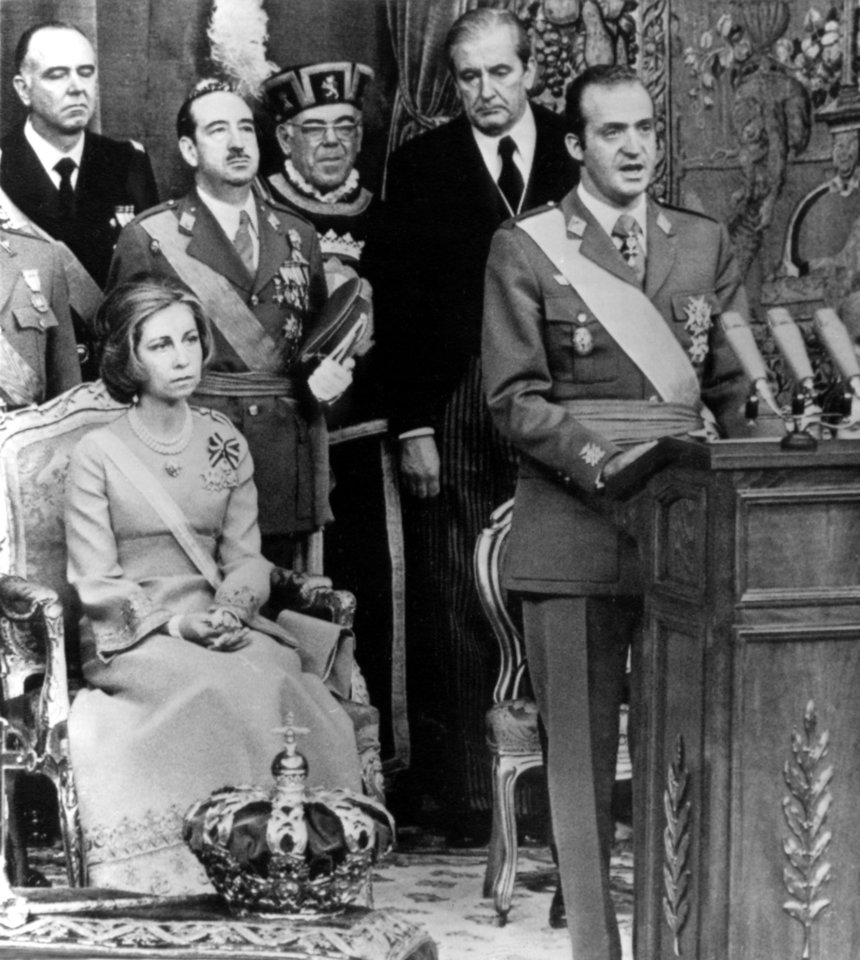 Photo - FILE - This is a Nov. 22, 1975 file photo King Juan Carlos speaks during his first official address as King  during a ceremony where he was crowned and proclaimed King of Spain.  Seated at left Queen Sofia. Spain's King Juan Carlos it was announced Monday June 2 2014 will abdicate and pave the way for his son, Crown Prince Felipe, to take over, Spanish Prime Minister Mariano Rajoy told the country Monday in an announcement broadcast nationwide.  He did not say when Juan Carlos would abdicate because the government must now craft a law creating a legal mechanism for the abdication and for 46-year-old Felipe's assumption of power.  The 76-year-old Juan Carlos oversaw his country's transition from dictatorship to democracy but has had repeated health problems in recent years.  (AP Photo/File)