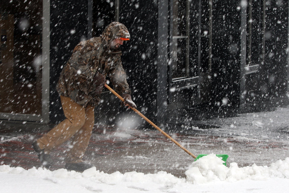 Photo - Brad Johnson pushes the heavy snow off the sidewalk in the blowing snow Thursday Dec. 20, 2012 in downtown Burlington, Iowa. (AP Photo/The Hawk Eye, John Gaines)