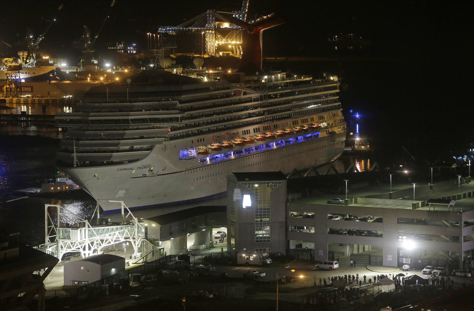 Photo - The cruise ship Carnival Triumph is pushed towards the cruise terminal along the Mobile River in Mobile, Ala., Thursday, Feb. 14, 2013. The ship with more than 4,200 passengers and crew members was idled for nearly a week in the Gulf of Mexico following an engine room fire. (AP Photo/Dave Martin)
