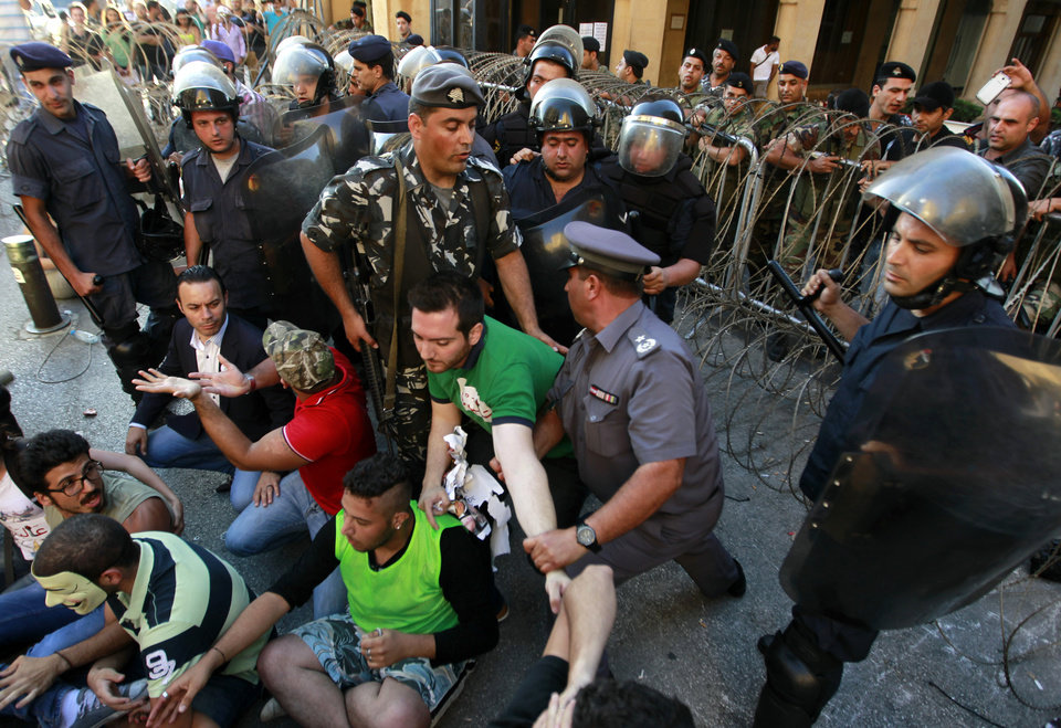 Photo - Lebanese riot police scuffle with civil society protesters near Parliament during a demonstration protesting the extension of parliament's mandate, in Beirut, Lebanon, Friday, June 21, 2013. Lebanon's parliament on May 29 extended its term by a year and a half, skipping scheduled elections because of the country's deteriorating security linked to the civil war next door in Syria. (AP Photo/Bilal Hussein)