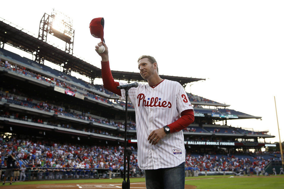 Photo - Former Philadelphia Phillies pitcher Roy Halladay tips his cap to the crowd after speaking before a baseball game against the New York Mets, Friday, Aug. 8, 2014, in Philadelphia. Halladay threw out the ceremonial first pitch in his first appearance at the stadium since retiring last season. (AP Photo/Matt Slocum)