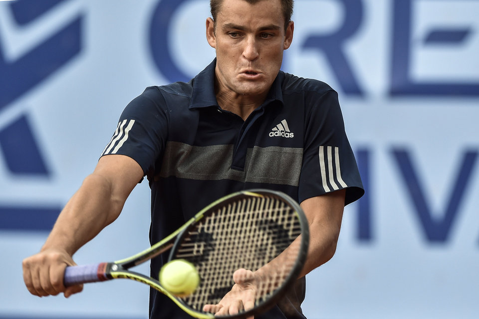 Photo - Mikhail Youzhny of Russia  returns a ball  to Kenny De Schepper of France during the second round match at the Suisse Open tennis tournament in Gstaad, Switzerland, Thursday, July 24, 2014. (AP Photo/Keystone,Peter Schneider)