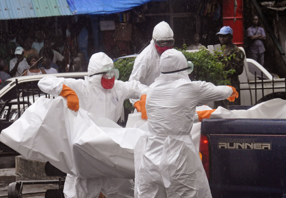 Photo - Health workers load the body of an amputee suspected of dying from the Ebola virus during the rain on the back of a truck, in a busy street in Monrovia, Liberia, Tuesday, Sept. 2, 2014.  Food in countries hit by Ebola is getting more expensive and will become scarcer because many farmers won't be able to access fields, a U.N. food agency warned Tuesday. An Ebola outbreak in West Africa has killed more than 1,500 people, and authorities have cordoned off entire towns in an effort to halt the virus' spread.  (AP Photo/Abbas Dulleh)