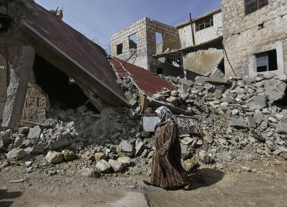 A Syrian woman walks past a house destroyed from a government airstrike, at Jabal al-Zaweya village of Sarjeh, in Idlib, Syria, Monday Feb. 25, 2013. Syria is ready to hold talks with the armed opposition trying to topple President Bashar Assad, the country\'s foreign minister said Monday, in the government\'s most advanced offer yet to try to resolve the 2-year-old civil war through negotiations. (AP Photo/Hussein Malla)