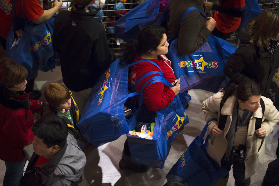 A shopper carries bags stuffed with toys in the Times Square Toys-R-Us store after doors were opened to the public at 8 p.m. on Thursday, Nov. 22, 2012, in New York. While stores typically open in the wee hours of the morning on the day after Thanksgiving known as Black Friday, openings have crept earlier and earlier over the past few years. Now, stores from Wal-Mart to Toys R Us are opening their doors on Thanksgiving evening, hoping Americans will be willing to shop soon after they finish their pumpkin pie. (AP Photo/John Minchillo)