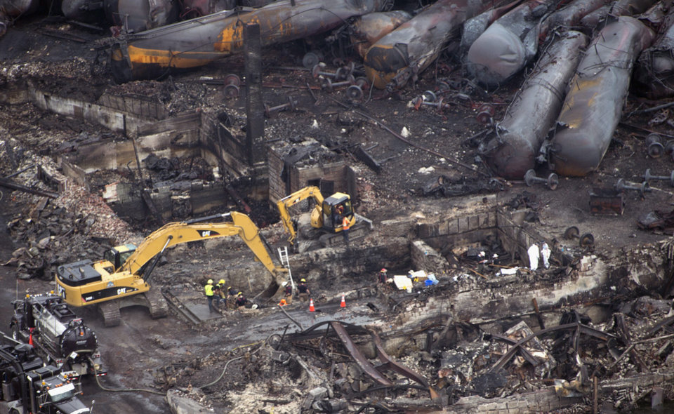 Photo - Workers comb through the debris Tuesday, July 9, 2013 in Lac-Magantic, Quebec.  The fiery oil train derailment early Saturday caused explosions and fires that devasted the town.  (AP Photo/The Canadian Press, Paul Chiasson)
