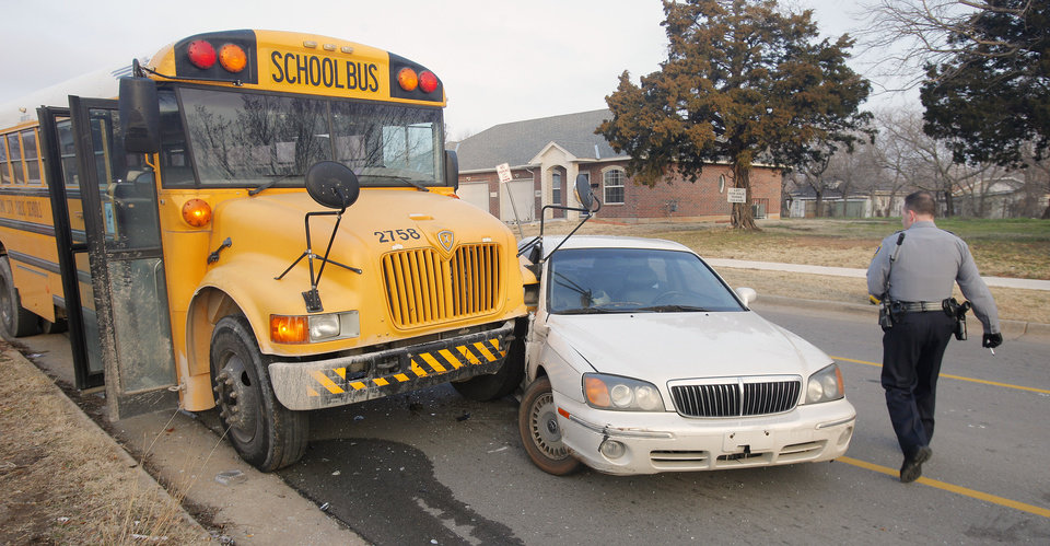 An Oklahoma City police officer investigates a wreck after the driver of a car made an improper right turn and was hit by an Oklahoma City School bus on NE 16 Street at Lottie Avenue in Oklahoma City Thursday, Feb. 16, 2012. Photo by Paul B. Southerland, The Oklahoman
