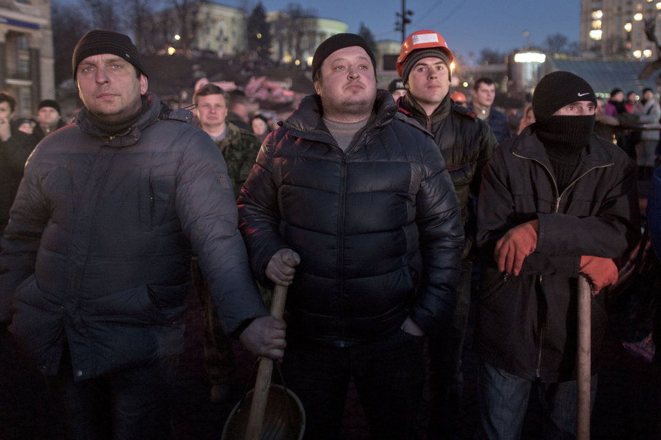 Photo - Anti-government protesters watch a live broadcast from the parliament in central Kiev, Ukraine, Friday, Feb. 21, 2014.  European officials say Ukrainian protesters have agreed to a deal with Ukraine's president on defusing a deadly political crisis. Earlier Friday President Viktor Yanukovych announced early elections and promised to invite the opposition into the government. (AP Photo/Darko Bandic)
