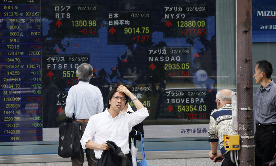 Photo -   A man waits to cross a road as others watch a digital display of global stock indexes outside a securities firm in Tokyo Monday, July 2, 2012. Asian stock markets inched higher Monday amid continued optimism over Europe's moves to ease its debt crisis and economic malaise. (AP Photo/Koji Sasahara)