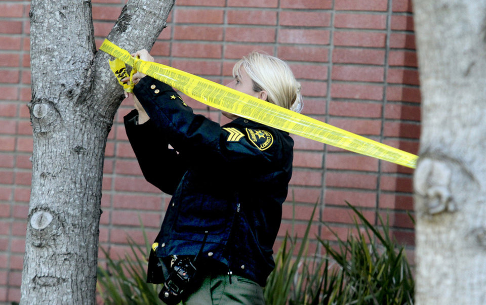 Photo - A Santa Cruz County Sheriffs sergeant tapes off an area on a North Branciforte Avenue property near the spot where Jeremy Goulet allegedly murdered Santa Cruz Police detectives Elizabeth Butler and Loran 'Butch Baker on Tuesday in Santa Cruz, Calif., on Wednesday, Feb. 27, 2013. (AP Photo/Santa Cruz Sentinel, Shmuel Thaler)