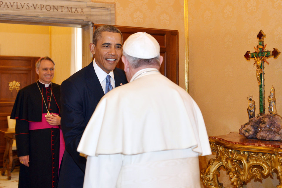 Photo - Pope Francis welcomes President Barack Obama as Archbishop George Gaenswein, background left, look at them, at the Vatican Thursday, March 27, 2014. President Barack Obama is holding a historic first meeting with Pope Francis, the pontiff that the president views as a kindred spirit on issues of economic inequality and the poor. Obama arrived at the Vatican Thursday morning amid the pomp and tradition of the Catholic Church, making his way to greet the pope after a long slow procession. (AP Photo/Gabriel Bouys, Pool)