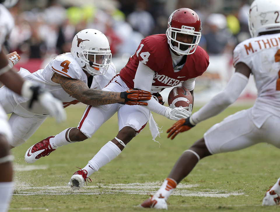 Photo - OU's Jalen Saunders (14) gets past UT's Kenny Vaccaro (4) during the Red River Rivalry college football game between the University of Oklahoma (OU) and the University of Texas (UT) at the Cotton Bowl in Dallas, Saturday, Oct. 13, 2012. Oklahoma won 63-21. Photo by Bryan Terry, The Oklahoman