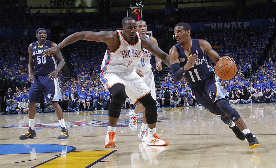 Photo - Memphis' Mike Conley (11) drives past Oklahoma City's Kendrick Perkins (5) during game one of the Western Conference semifinals between the Memphis Grizzlies and the Oklahoma City Thunder in the NBA basketball playoffs at Oklahoma City Arena in Oklahoma City, Sunday, May 1, 2011. Photo by Chris Landsberger, The Oklahoman