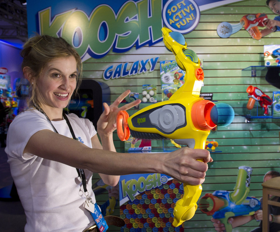 """FILE - In this Saturday, Feb. 11, 2012 file photo provided by Hasbro, toy demonstrator Marnye Young practices with the """"Koosh Alien Archer"""" ball launcher at Hasbro's American International Toy Fair showroom in New York. Toy maker Hasbro says its fourth-quarter revenue failed to meet expectations because of weaker-than-expected demand over the holidays. It plans to cut about 10 percent of its workforce and consolidate facilities to cut expenses. The stock dropped more than 4 percent in premarket trading Friday, Jan. 25, 2013. (AP Photo/Hasbro, Ray Stubblebine, File)"""