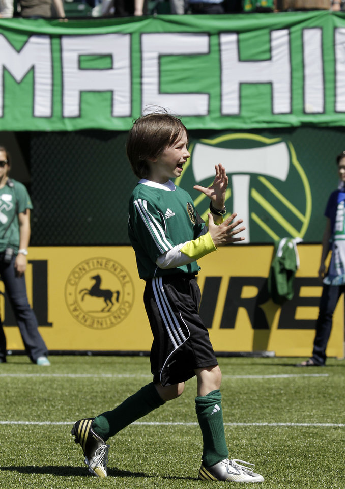 Photo - Atticus Lane-Dupre, 8, celebrates after scoring a goal as his team, the Green Machine, play against the MLS Portland Timbers soccer team in Portland, Ore., Wednesday, May 1, 2013.  The Timbers and Make-A-Wish Oregon treated Atticus' team to a game at Jeld-Wen Field with more than 3,000 fans coming out to lend their support. Atticus missed the Green Machine's final match last fall because of cancer treatment.  (AP Photo/Don Ryan)