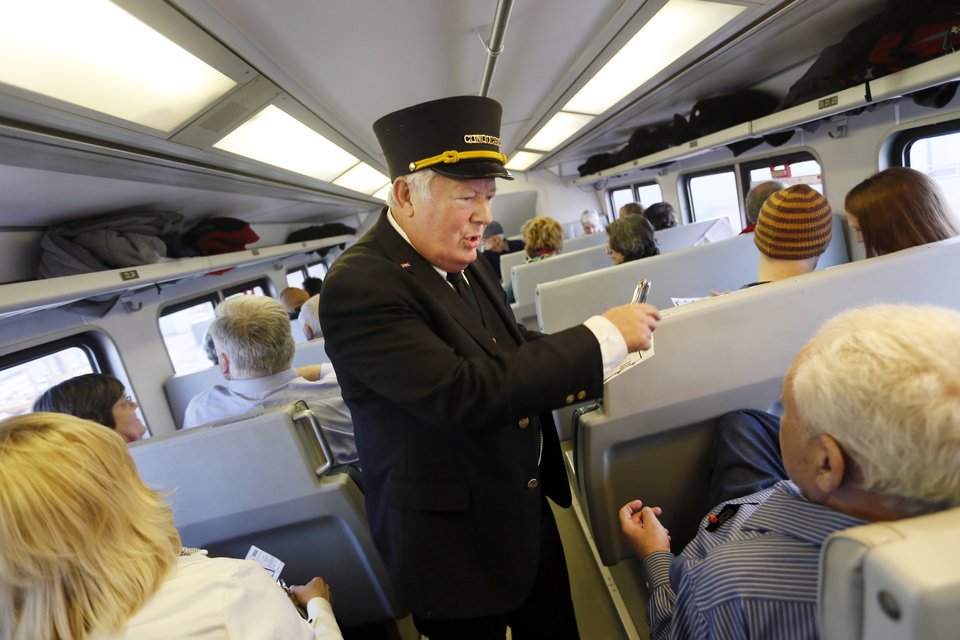 Photo - Conductor Neil Bagaus of Orlando, Fla.,  talks with passengers as he punches tickets on a demonstration ride of the Eastern Flyer passenger train from Sapulpa to the Oklahoma City metro area, Sunday, Feb. 23, 2014. Photo by Nate Billings, The Oklahoman
