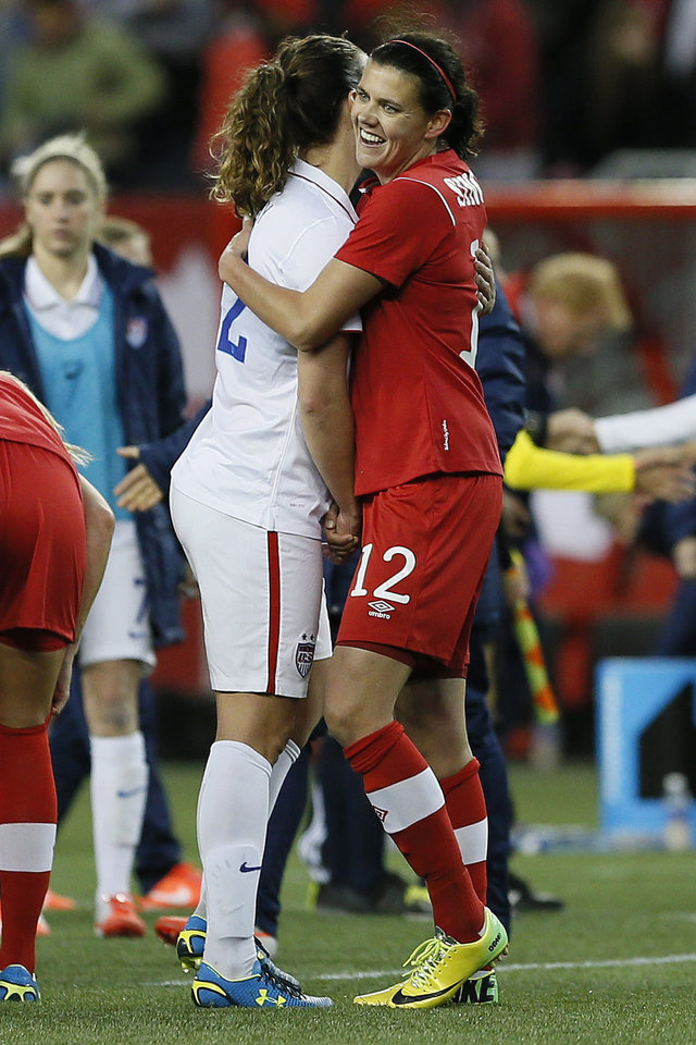 Photo - Canada's forward Christine Sinclair (12) and USA's midfielder Lauren Holiday (12) embrace after a 1-1 tie in an exhibition soccer match in Winnipeg, Manitoba, Thursday, May 8, 2014. (AP Photo/The Canadian Press, John Woods)
